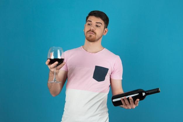 Geschokte jonge man die naar een glas wijn kijkt.