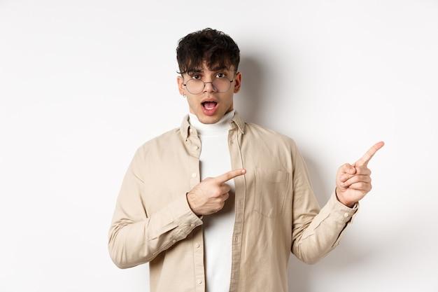 Geschokte jonge man met een bril die met zijn vingers naar de lege ruimte wijst, vragen stelt over advertenties, staande op een witte achtergrond