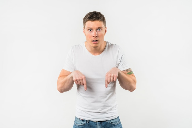 Geschokte jonge mens die haar vingers neerwaartse tegen witte achtergrond richt