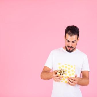 Geschokte jonge mens die open giftdoos bekijkt met gouden boog