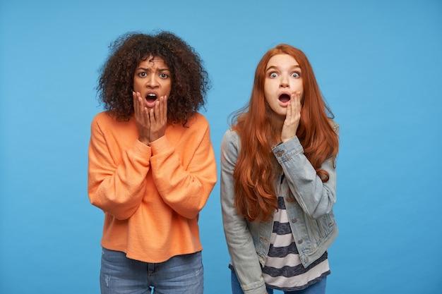 Geschokte jonge mooie dames met opgeheven handpalmen op hun gezicht en verbaasd kijken met grote ogen en mond open, poseren voor de blauwe muur