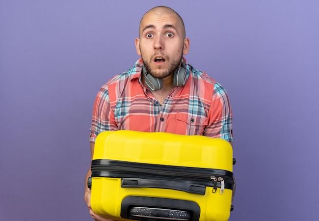Geschokte jonge reiziger man met koptelefoon om zijn nek met koffer geïsoleerd op paarse muur met kopieerruimte