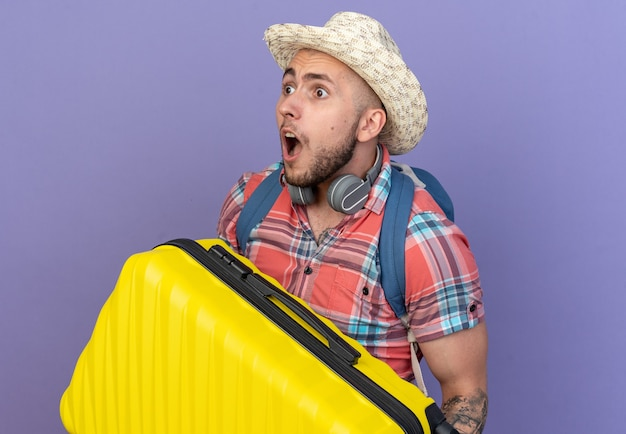 Geschokte jonge reiziger man met stro strand hoed en met rugzak met koffer kijkend naar kant geïsoleerd op paarse muur met kopie ruimte