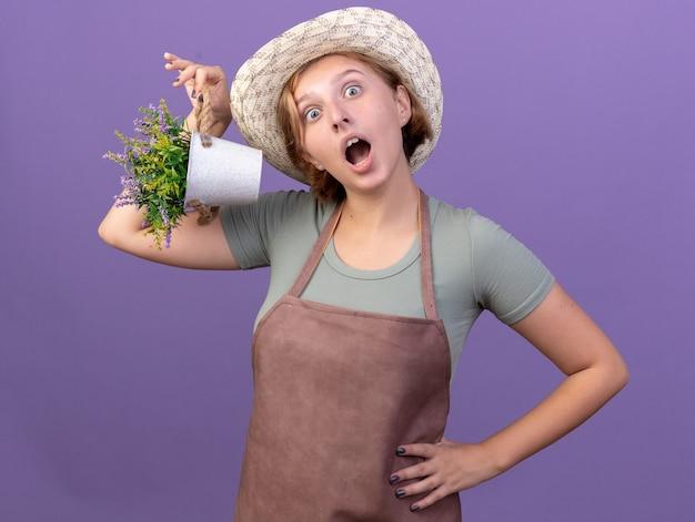 Geschokte jonge slavische vrouwelijke tuinman die een tuinhoed draagt met bloemen in een bloempot