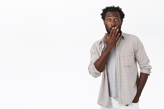 Geschokte jonge stijlvolle afro-amerikaanse man kijkt beschaamd of verrast, zeg oeps