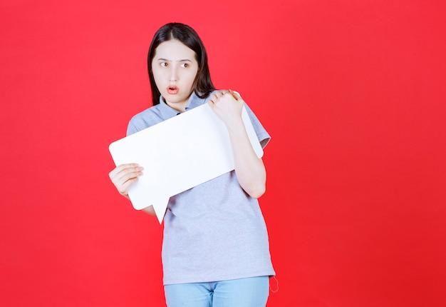 Geschokte jonge vrouw die een bord vasthoudt en naar de voorkant kijkt