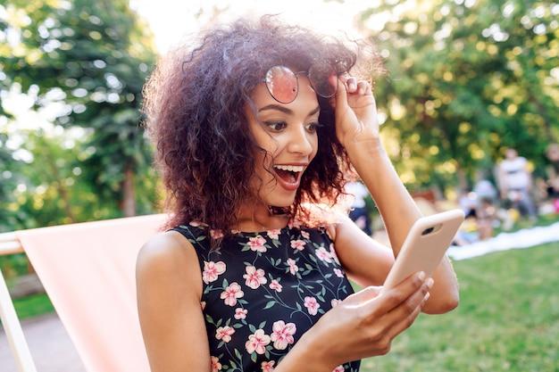 Geschokte jonge vrouw die met open mond op mobiele telefoon kijkt