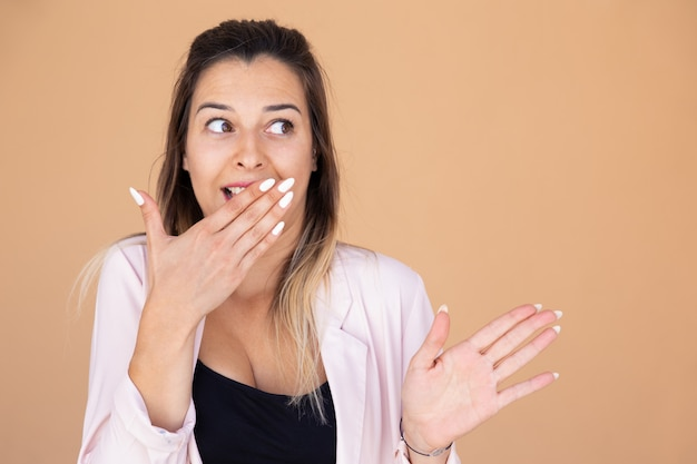 Geschokte jonge vrouw die mond behandelt met hand