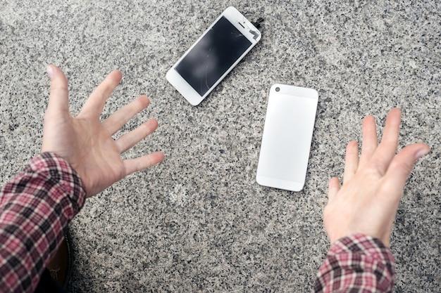 Geschokte jonge vrouw gooit haar handen in de lucht, ze liet zijn smartphone vallen en viel uit elkaar