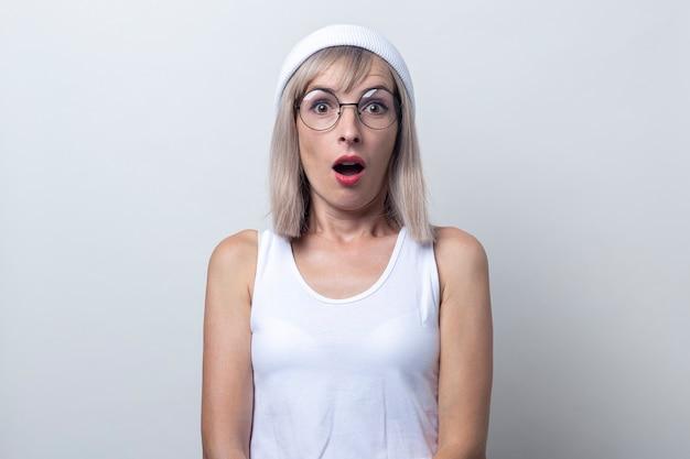 Geschokte jonge vrouw in een witte hoed en bril op een lichte achtergrond.