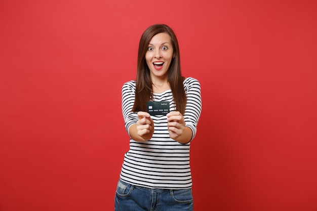 Geschokte jonge vrouw in gestreepte kleding die de mond wijd open houdt, er verrast uitziet, met een creditcard geïsoleerd op een rode muurachtergrond. mensen oprechte emoties, lifestyle concept. bespotten kopie ruimte.