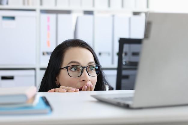 Geschokte jonge vrouw kijkt van onder tafel naar laptopmonitor. bange vrouw in paniek van internetnieuwsconcept