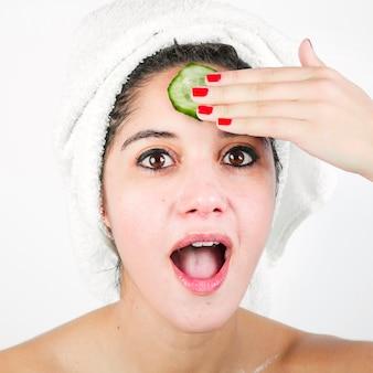 Geschokte jonge vrouw met komkommerplak over voorhoofd