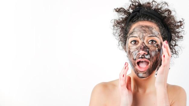 Geschokte jonge vrouw met zwart gezichtsmasker over haar die gezicht op witte achtergrond wordt geïsoleerd