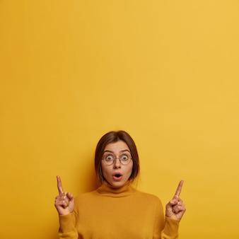 Geschokte jonge vrouw roddelt over het laatste nieuws, wijst beide wijsvingers naar boven, hoort verrassend nieuws, opent mond, draagt grote ronde bril en coltrui, geïsoleerd op gele muur