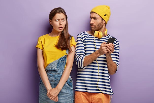 Geschokte jonge vrouw verdenkt vriendje van verraad, kijkt ongenoegen, probeert bericht in vriendjes smartphone te bekijken. stel een relatie uit