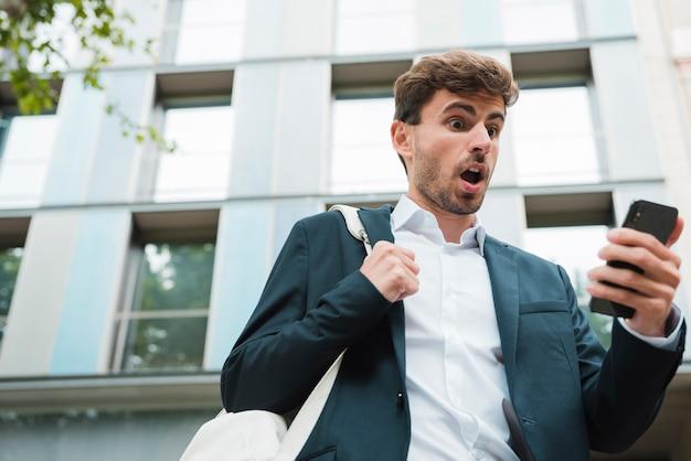 Geschokte jonge zakenman met zijn rugzak die mobiele telefoon bekijkt