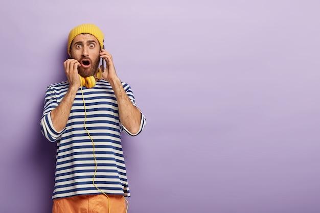 Geschokte jongeman plaatst bestelling via mobiel, stomverbaasd dat hij geen tafel in restaurant kan reserveren, kijkt met omg-uitdrukking, draagt modieuze outfit