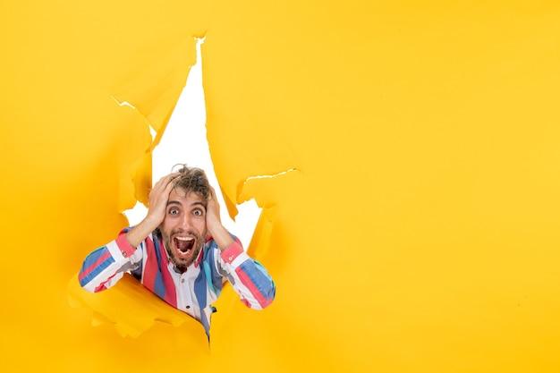 Geschokte jongeman poseert op een gescheurde gele papieren gatachtergrond