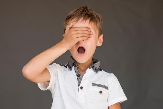 Geschokte jongen die zijn ogen behandelt