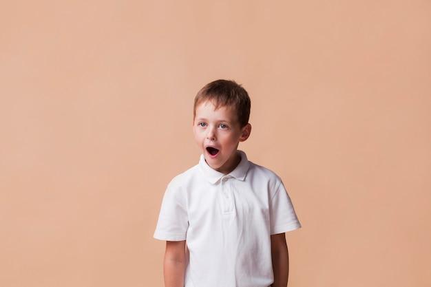 Geschokte jongen met mond open status dichtbij beige achtergrond