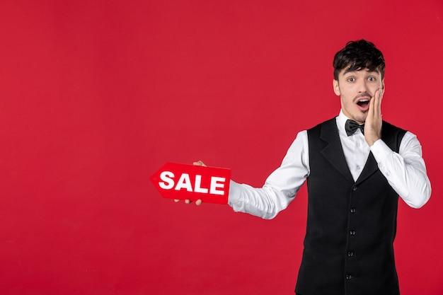Geschokte kerelkelner in een uniform met vlinder op hals die verkooppictogram op geïsoleerde rode achtergrond toont