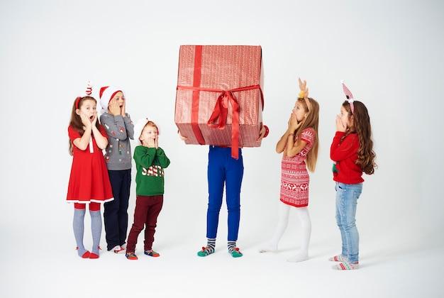 Geschokte kinderen kijken naar een enorm geschenk