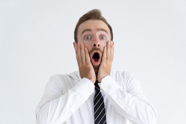 Geschokte knappe mens die mond open houdt en wangen raakt