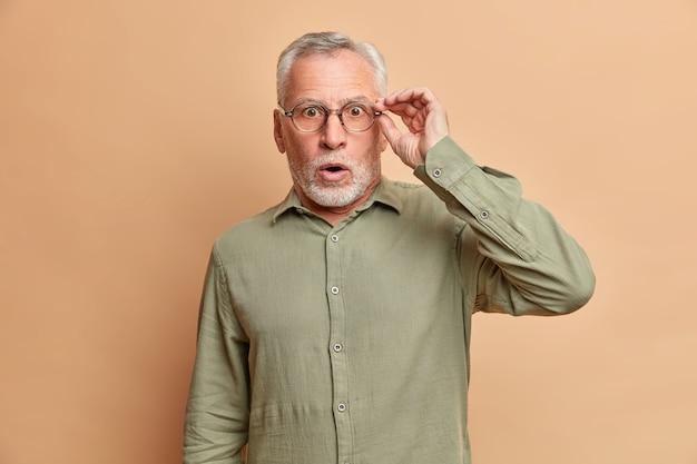 Geschokte knappe verdoofde bebaarde oudere man heeft grijs haar opent mond wijd houdt hand op bril kan niet geloven in schokkend nieuws draagt formele overhemdshoudingen tegen bruine studiomuur