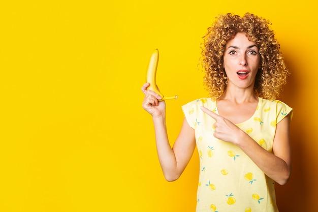 Geschokte krullende jonge vrouw die een banaan houdt die haar vinger op een gele achtergrond richt.