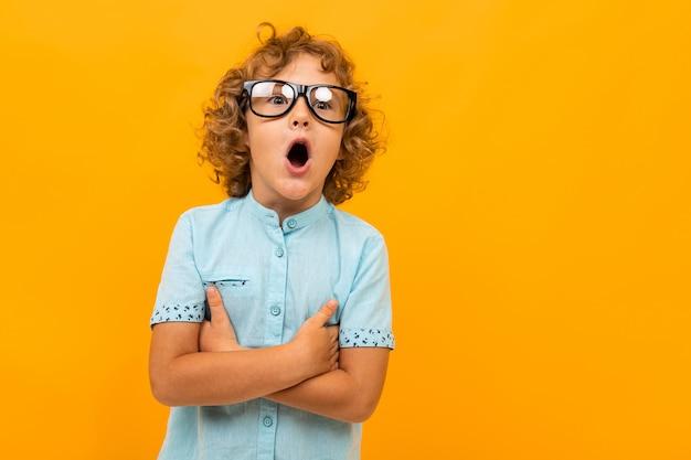 Geschokte krullende schooljongen met een bril op een geel