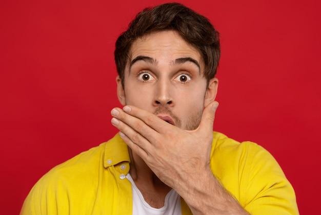 Geschokte man in geel overhemd voor mond, kijkt verrassend naar camera