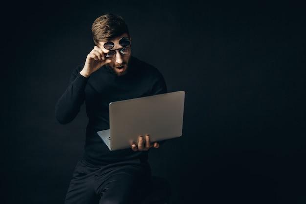 Geschokte man in glazen kijken naar laptop
