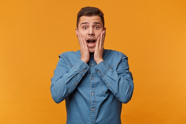 Geschokte man in paniek greep naar zijn gezicht, gekleed in een spijkeroverhemd, geïsoleerd op een gele muur