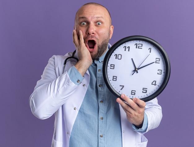 Geschokte mannelijke arts van middelbare leeftijd met een medisch gewaad en een stethoscoop die de klok vasthoudt en de hand op het gezicht houdt