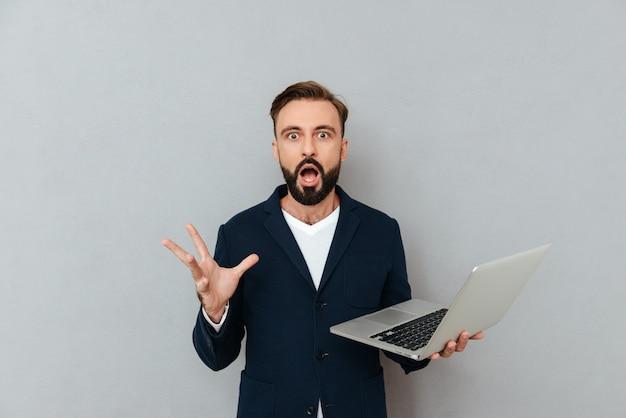 Geschokte mens die camera terwijl het houden van laptop computer kijkt