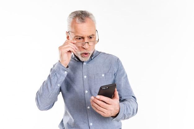 Geschokte mens die geïsoleerde smartphone bekijken