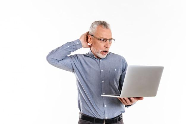 Geschokte mens in oogglazen die laptop geïsoleerde computer met behulp van