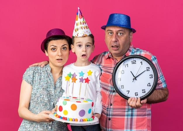 Geschokte moeder en zoon met feestmutsen die verjaardagstaart bij elkaar houden staande met vader die klok vasthoudt geïsoleerd op roze muur met kopieerruimte