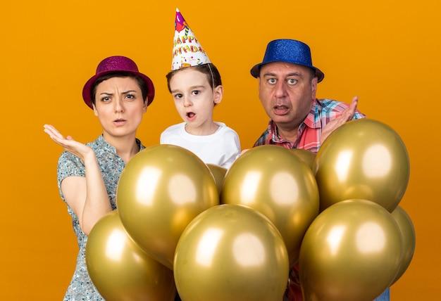 Geschokte moeder, zoon en vader met feestmutsen die staan met heliumballonnen die de handen open houden geïsoleerd op een oranje muur met kopieerruimte