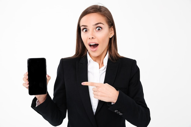 Geschokte mooie onderneemster die vertoning van mobiele telefoon toont