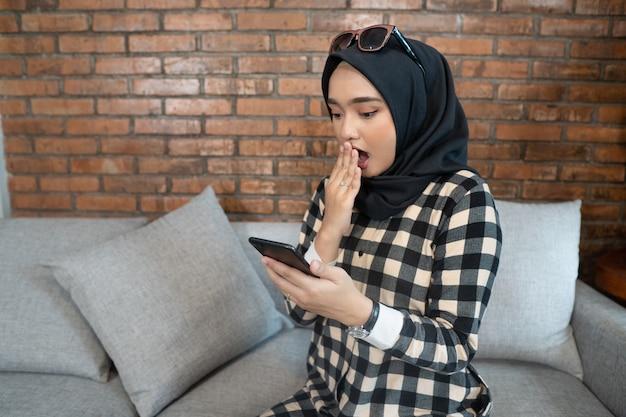 Geschokte moslimvrouw die haar telefoon bekijkt