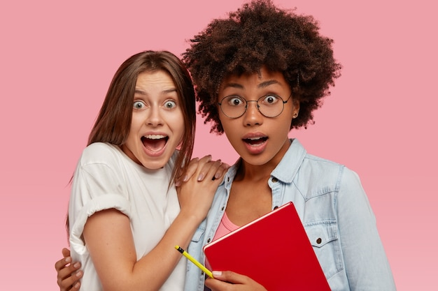 Geschokte multiethinc vrouwelijke studenten staan dicht bij elkaar, reageren actief op plotseling nieuws, omhelzen en houden leerboek vast, geïsoleerd over roze muur. etnische diversiteit concept. bang schoolmeisjes binnen