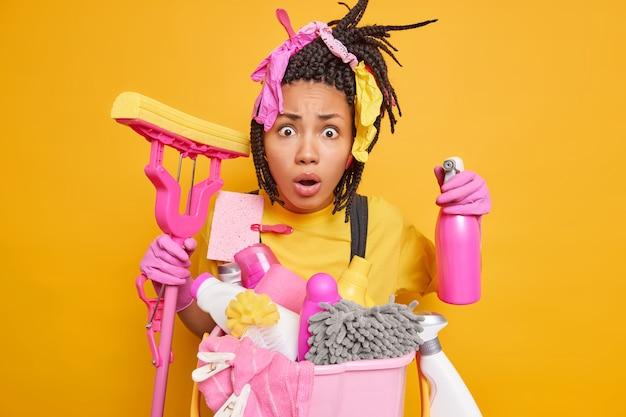 Geschokte nerveuze vrouw poseert met wasmiddel en schoonmaakaccessoires