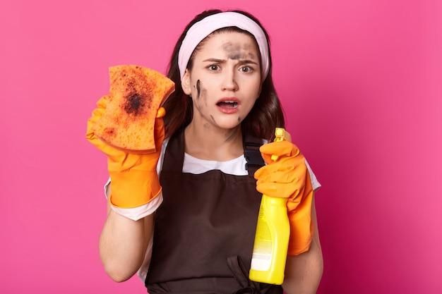 Geschokte onder de indruk schattige jonge dame die vuil washandje toont, wasmiddel in gele fles houdt, wijd openende mond, witte handband, bruine schort en casual t-shirt draagt. huishoudelijk concept.
