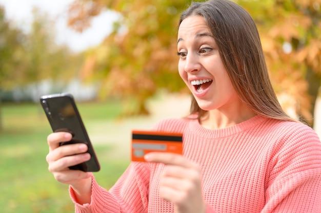 Geschokte online shopper met creditcard en mobiele telefoon die op straat betalen voor aankopen