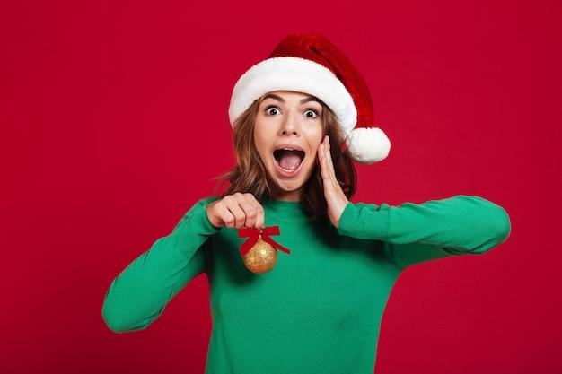 Geschokte opgewekte jonge dame die de hoed van kerstmissanta draagt