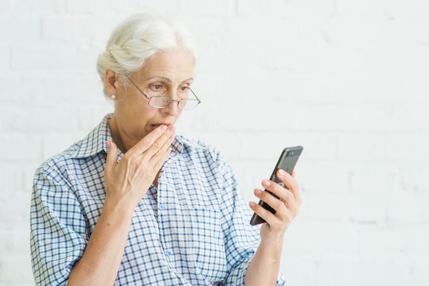 Geschokte oude vrouw die mobiel tegen achtergrond bekijkt