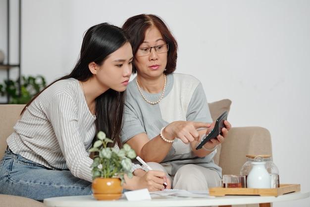 Geschokte oudere vrouw die rekenmachine met belachelijk groot getal aan haar dochter laat zien nadat ze alle kosten had opgeteld