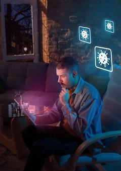 Geschokte, overstuur en verdrietige blanke man die gadgets gebruikt om informatie te krijgen over de verspreiding van een coronaviruspandemie. thuisblijven om veilig te zijn. analyseren van de situatie met 's werelds telling van gevallen, gezondheidszorg, medicijnen.